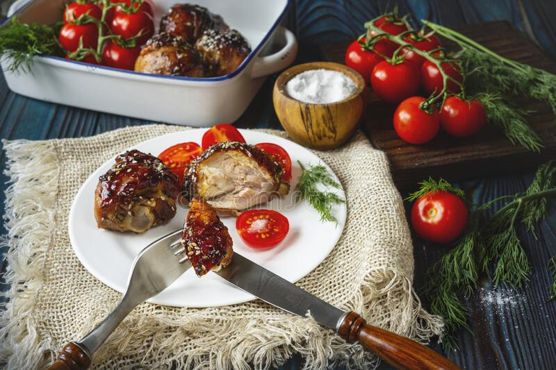 Roasted chicken and tomatoes on a white plate. royalty free stock images