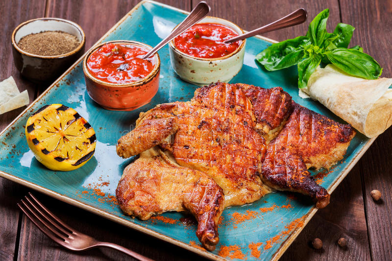 Roasted Chicken or turkey with spices, lemon, tomato sauce, basil and pita bread on plate on dark wooden background. Thanksgiving stock photography