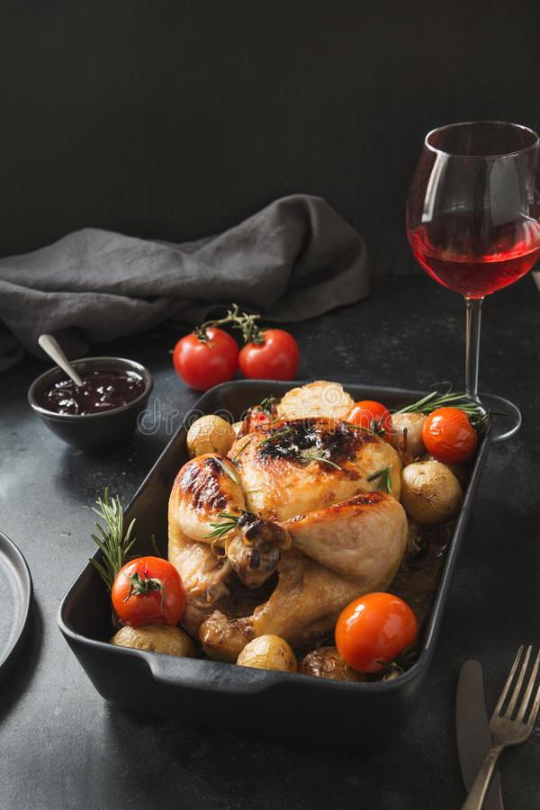 Roasted chicken with vegetables and wine glass on black. Oven baked food. Roasted chicken with vegetables and wine glass on black table. Dinner. Oven baked food royalty free stock photo