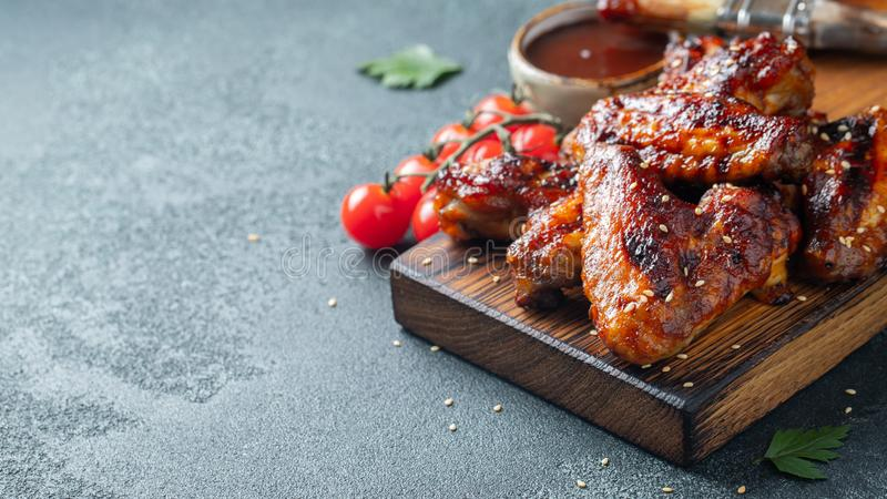 Roasted chicken wings in barbecue sauce with sesame seeds and parsley on a wooden board on a concrete table. With copy royalty free stock images
