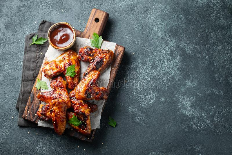 Roasted chicken wings in barbecue sauce with sesame seeds and parsley on a wooden board on a concrete table. Top view stock photos