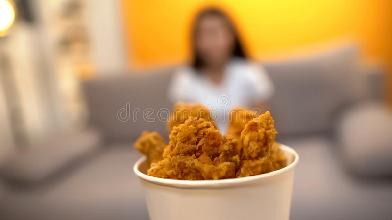 Roasted chicken wings on foreground, girl sitting at home, junk food delivery royalty free stock photo