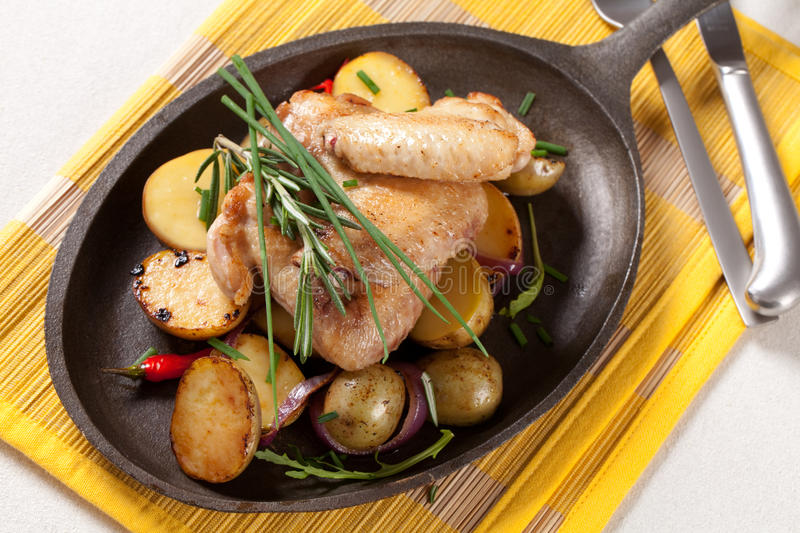 Roasted chicken wings and potatoes royalty free stock photo