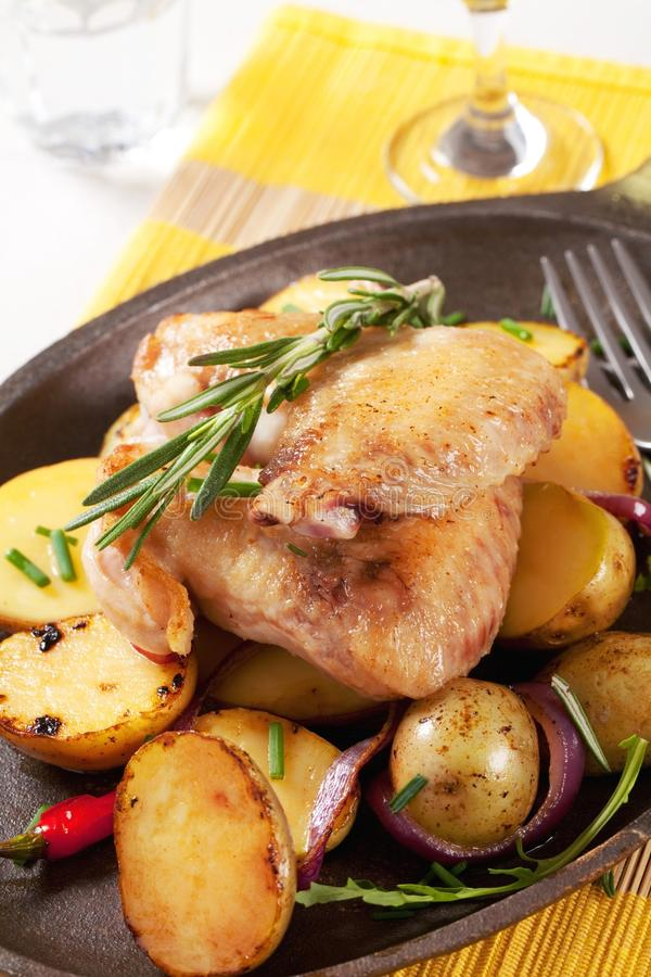 Roasted chicken wings and potatoes stock image
