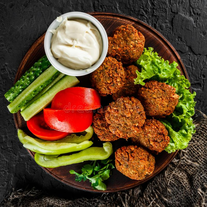 Roasted chickpeas falafel patties with garlic yogurt sauce, served with lettuce and fresh vegetables in a plate over dark stone. Background. Healthy vegan food royalty free stock photography