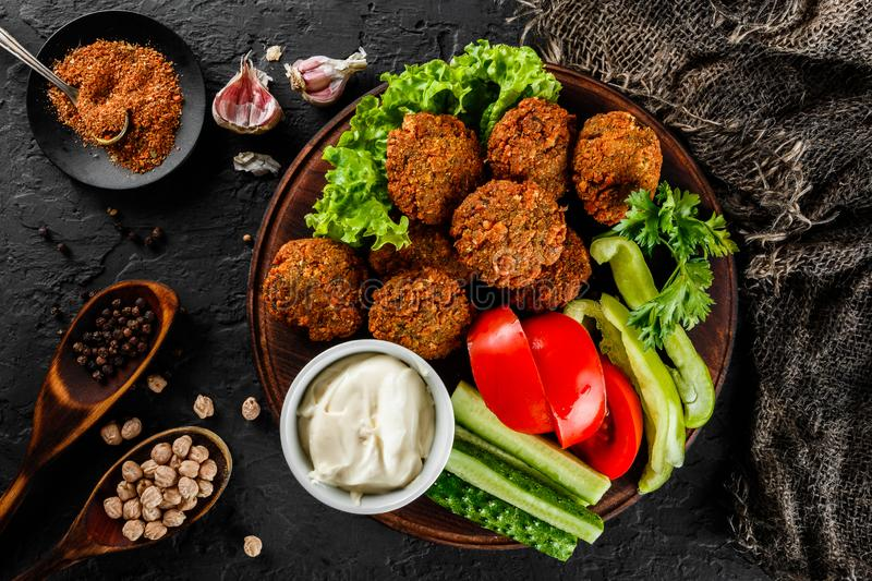 Roasted chickpeas falafel patties with garlic yogurt sauce, served with lettuce and fresh vegetables in a plate over dark stone. Background. Healthy vegan food stock photography