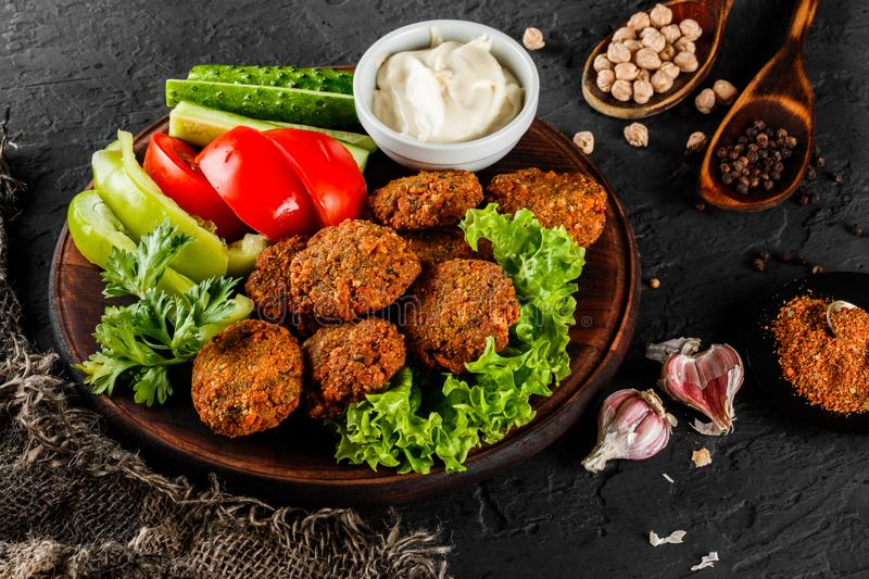 Roasted chickpeas falafel patties with garlic yogurt sauce, served with lettuce and fresh vegetables in a plate over dark stone. Background. Healthy vegan food royalty free stock image