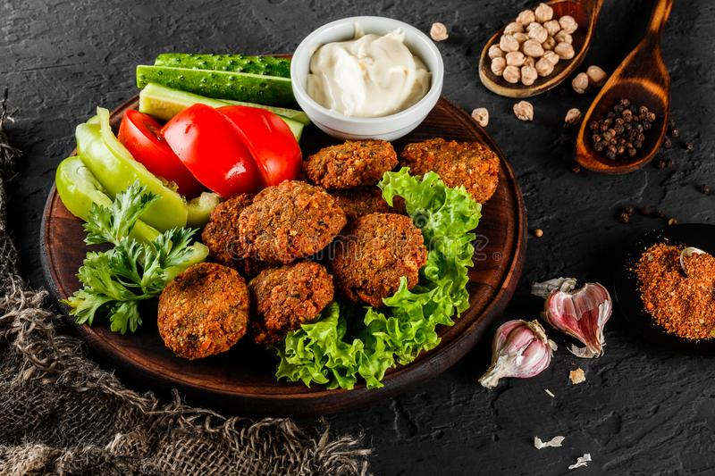 Roasted chickpeas falafel patties with garlic yogurt sauce, served with lettuce and fresh vegetables in a plate. Over dark stone background. Healthy vegan food royalty free stock photo