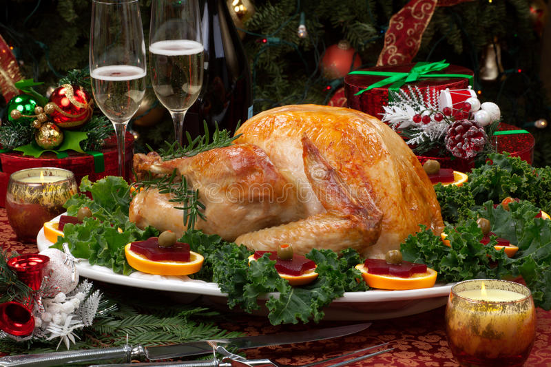 Roasted Christmas Turkey. Christmas-decorated table with feast, gifts, roasted turkey, candles, champagne, and Christmas tree on back royalty free stock photo