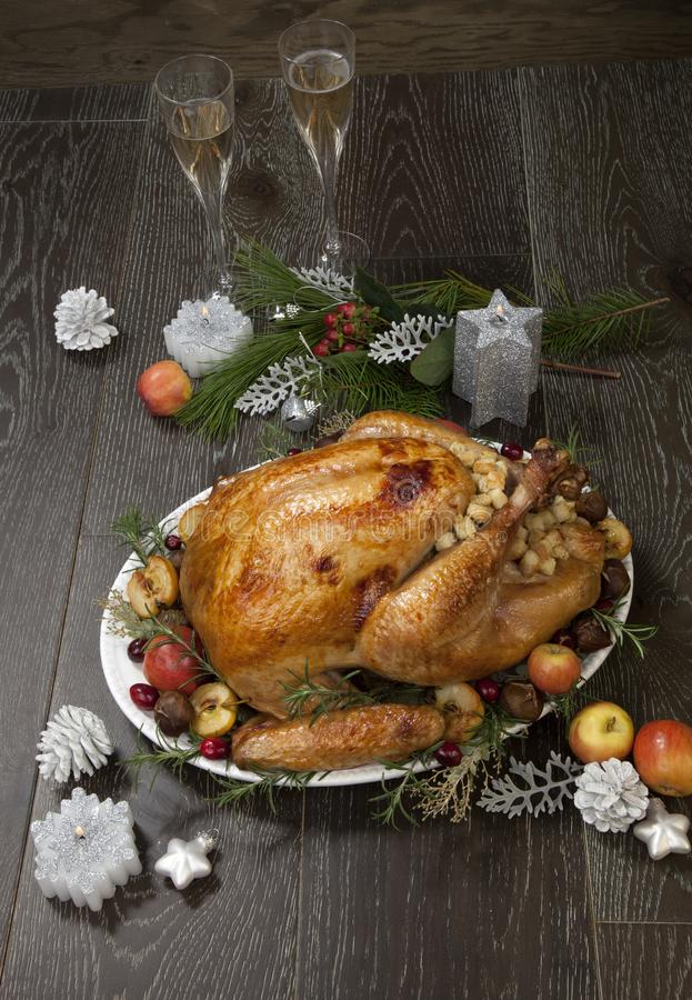 Roasted Christmas Turkey with Grab Apples. Garnished roasted Christmas turkey with grab apples, sweet chestnut, cranberry, Christmas ornaments, candles, and pine royalty free stock image