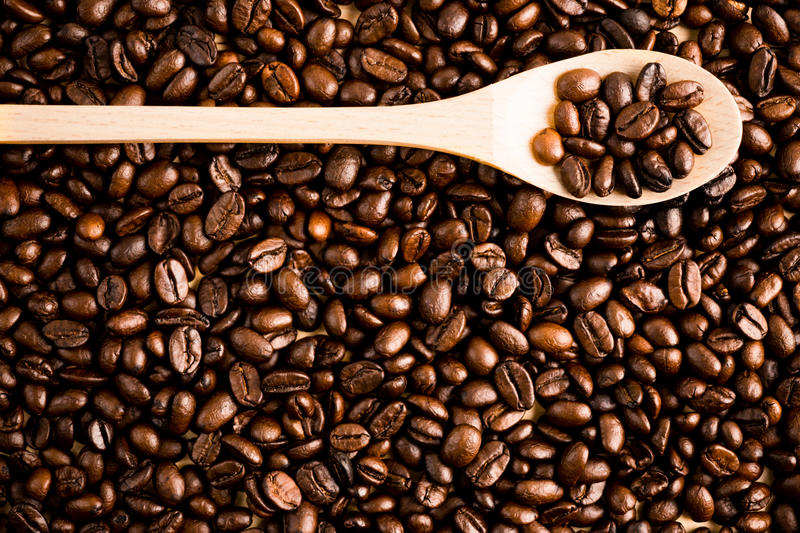 Roasted coffee bean background and texture with wooden spoon, co stock photos