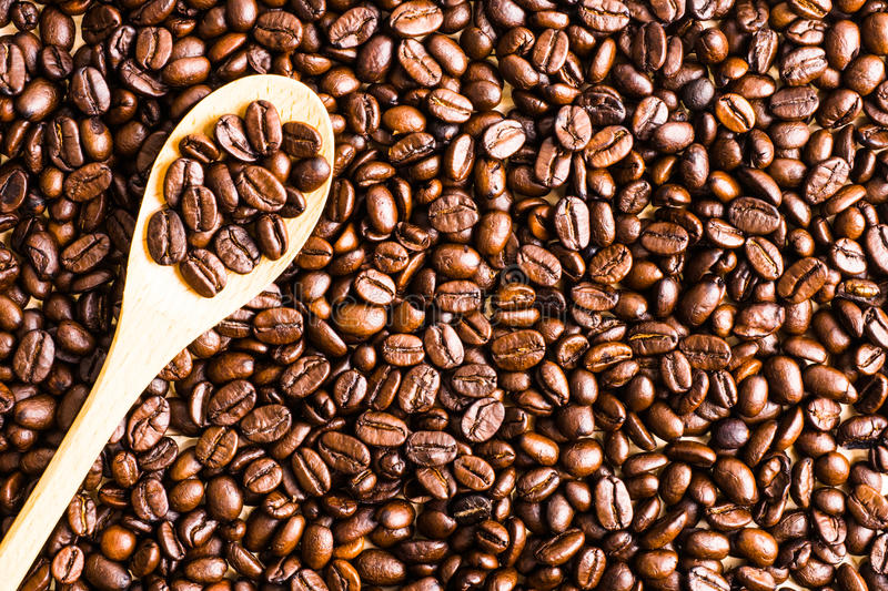 Roasted coffee bean background and texture with wooden spoon, co stock image