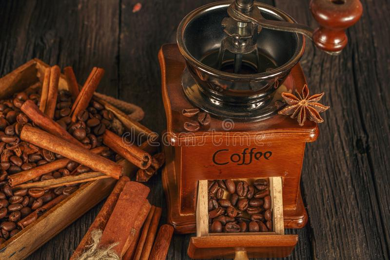 Roasted coffee bean with cinnamon and coffee grinder on wooden background. Coffee beans with cinnamon chopsticks on a black wooden stock image