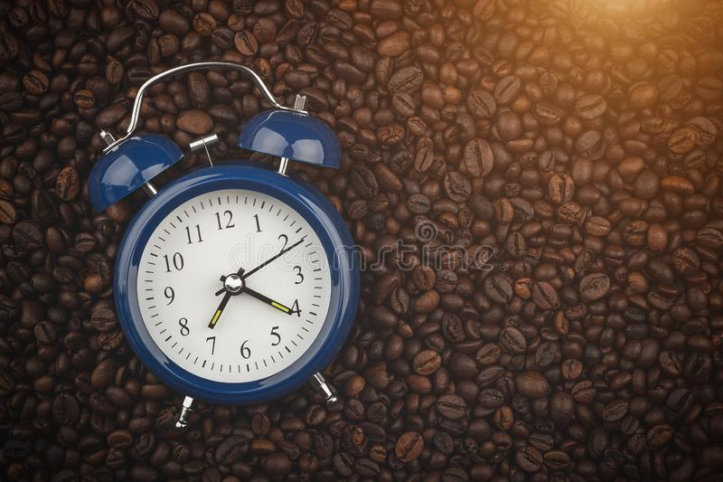 Roasted coffee beans and alarm clock. Wake up. Good morning. Background, close-up view. Healthy lifestyle. Energy drink. Good morning. Coffee store. Cafe. Copy stock photos
