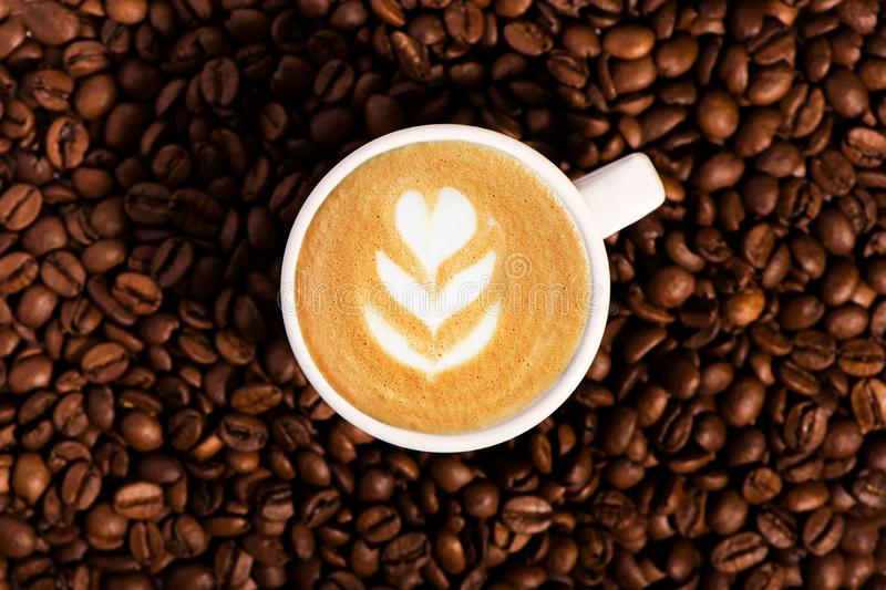 Roasted coffee beans background with cup of coffee with latte art. stock photography