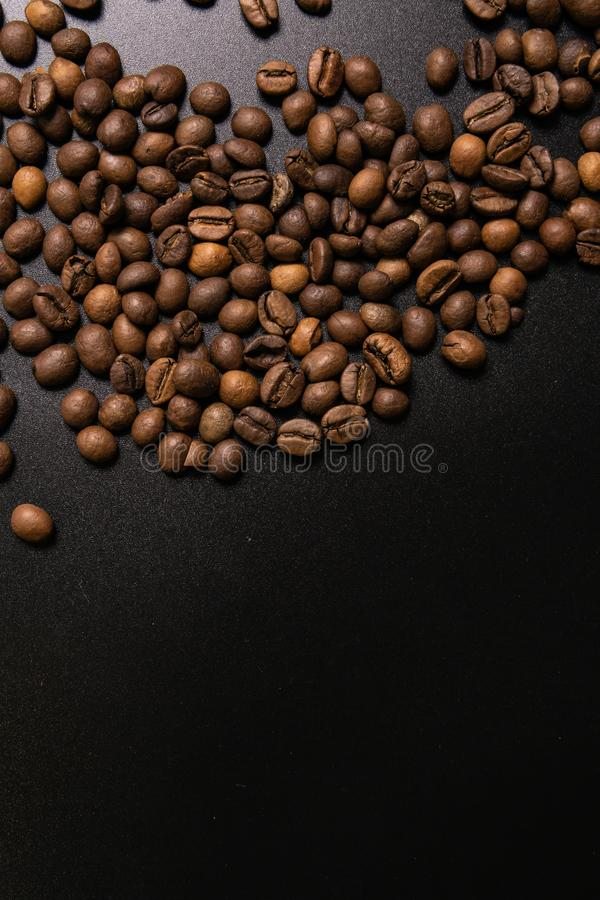 Roasted coffee beans in bulk on a black background. dark cofee roasted grain flavor aroma cafe, natural coffe shop background, top stock photography