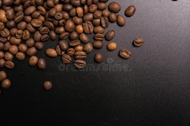 Roasted coffee beans in bulk on a black background. dark cofee roasted grain flavor aroma cafe, natural coffe shop background, top stock photo