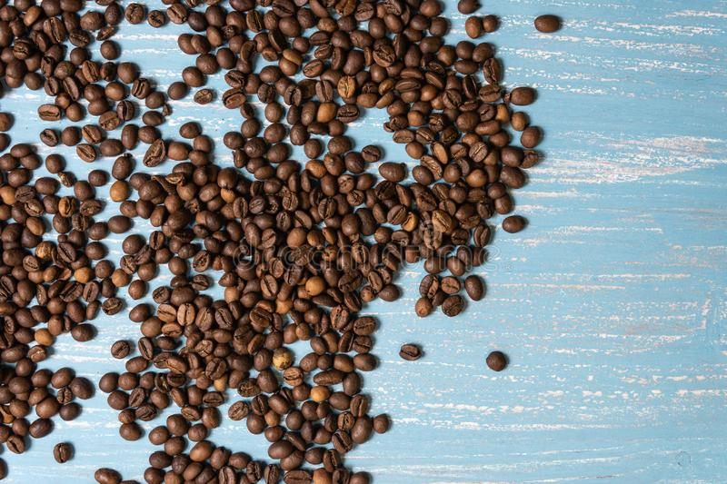 Roasted coffee beans in bulk on a blue wooden background. dark cofee roasted grain flavor aroma cafe, natural coffe shop royalty free stock photography
