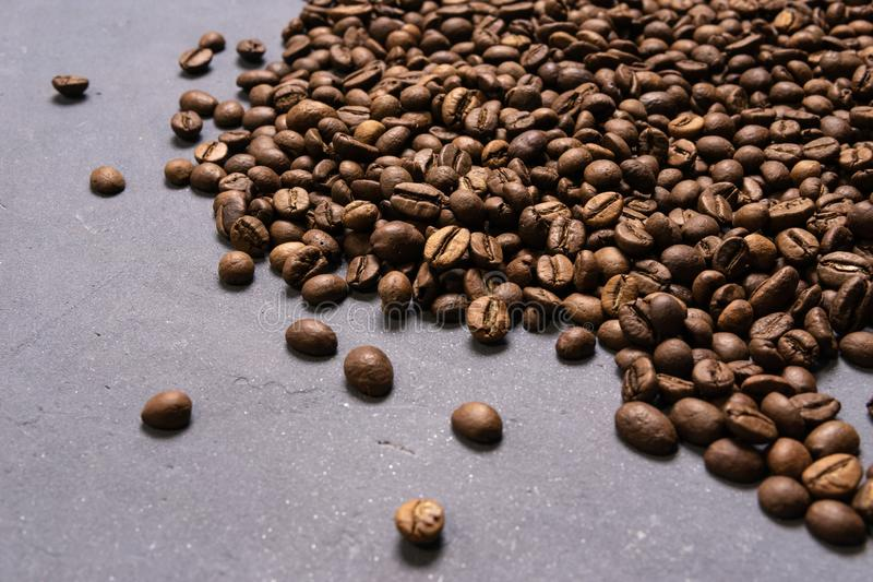 Roasted coffee beans in bulk on a gray concrete background. dark cofee roasted grain flavor aroma cafe, natural coffe shop stock photo