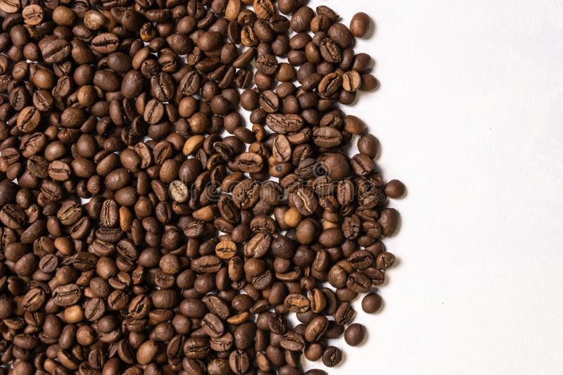 Roasted coffee beans in bulk on a light blue background. dark cofee roasted grain flavor aroma cafe, natural coffe shop background stock photo