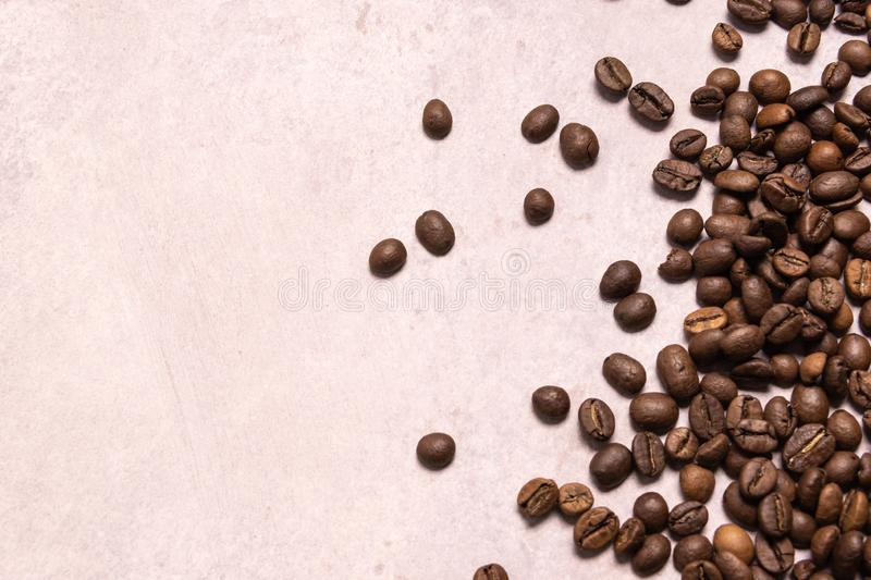 Roasted coffee beans in bulk on a light pink background. dark cofee roasted grain flavor aroma cafe, natural coffe shop background stock photo