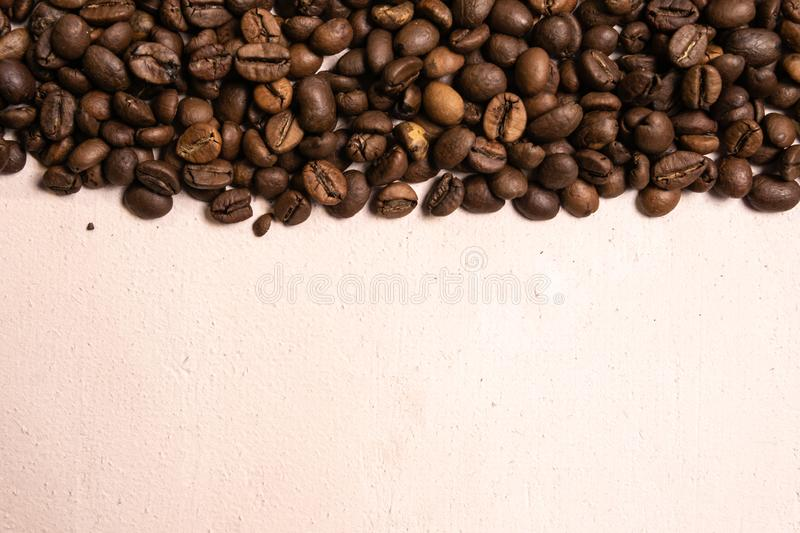 Roasted coffee beans in bulk on a light pink background. dark cofee roasted grain flavor aroma cafe, natural coffe shop background royalty free stock image