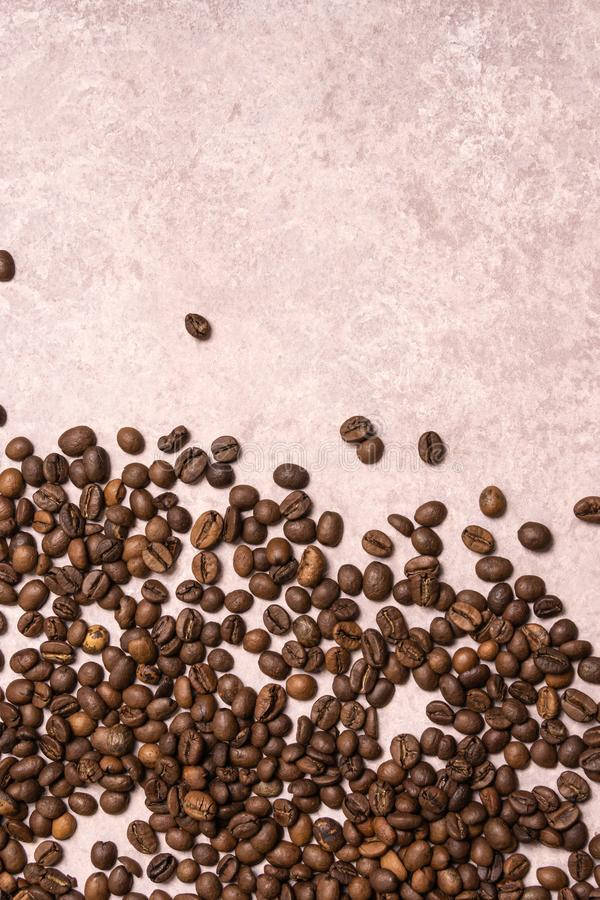 Roasted coffee beans in bulk on a light pink background. dark cofee roasted grain flavor aroma cafe, natural coffe shop background royalty free stock images