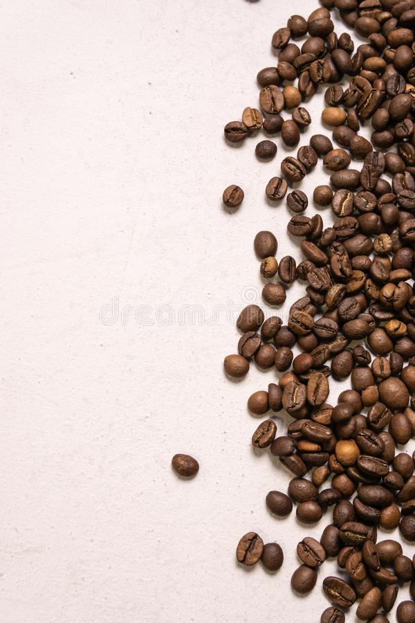 Roasted coffee beans in bulk on a light pink background. dark cofee roasted grain flavor aroma cafe, natural coffe shop background stock photos