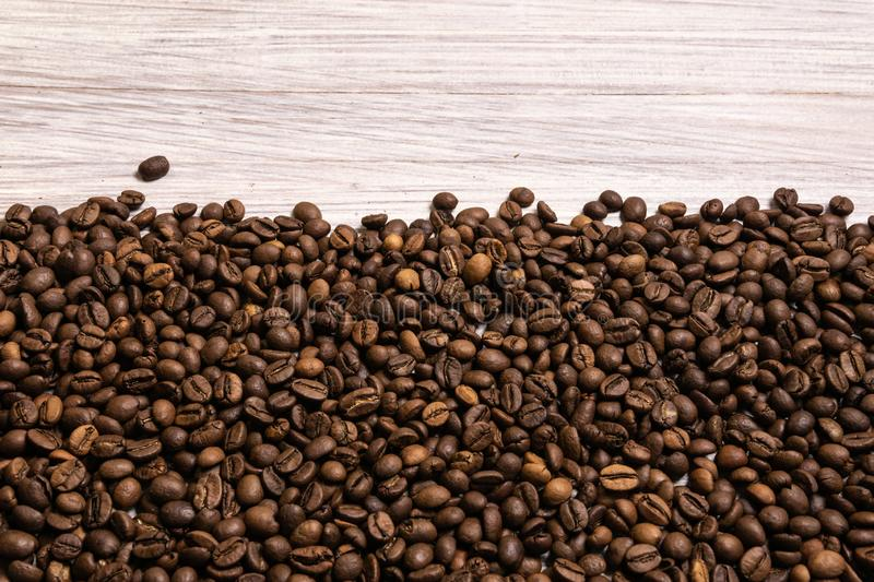Roasted coffee beans in bulk on a light wooden background. dark cofee roasted grain flavor aroma cafe, natural coffe shop royalty free stock photo