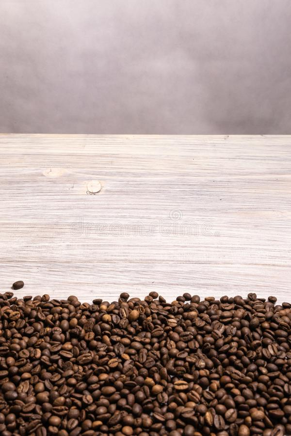 Roasted coffee beans in bulk on a light wooden background. dark cofee roasted grain flavor aroma cafe, natural coffe shop royalty free stock photography