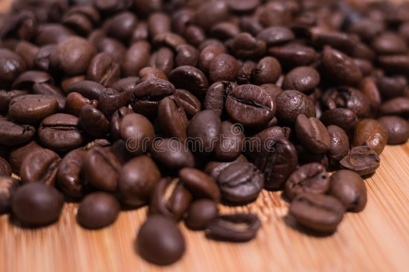 Roasted Coffee Beans close up / macro view on natural wooden background royalty free stock images