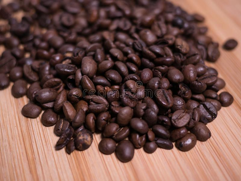Roasted Coffee Beans close up view on natural wooden background stock photo