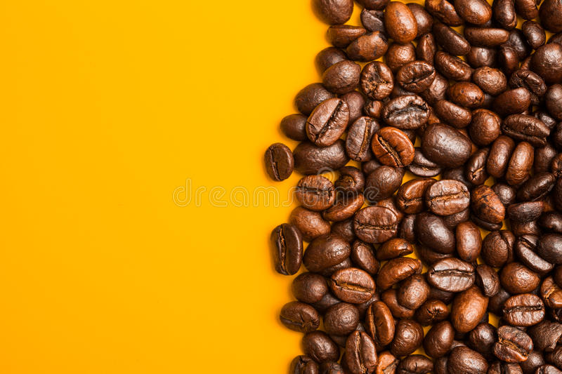 Roasted coffee beans close up. Yellow background. Space for text stock image