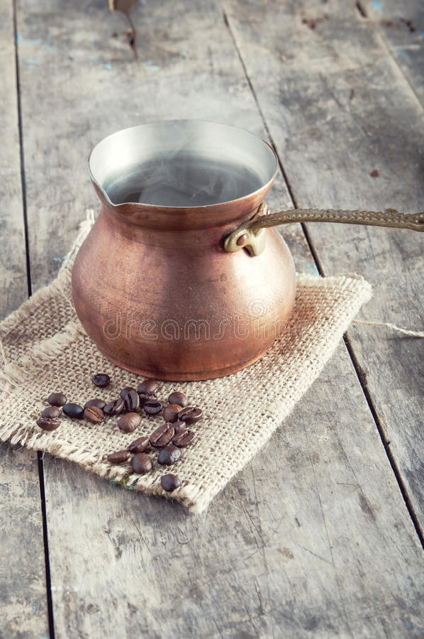 Roasted coffee beans and copper coffee pot royalty free stock images
