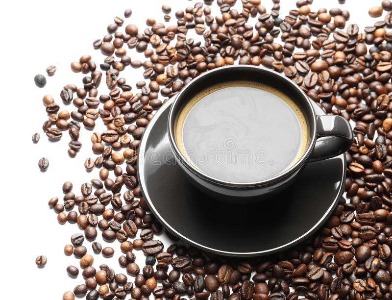 Roasted coffee beans and cup of hot beverage. On white background royalty free stock photo