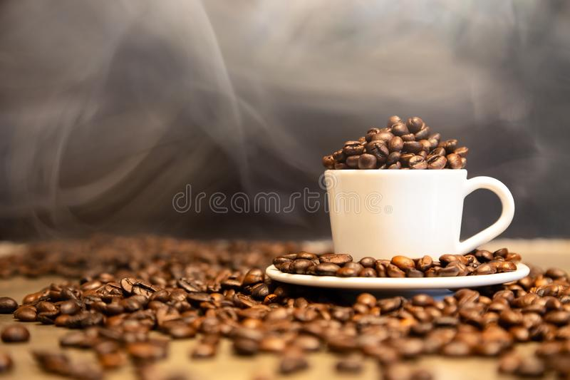 Roasted coffee beans in a cup of hot espresso,arabica coffee beans and robusta coffee beans mixed,medium roasted to dark roasted royalty free stock images