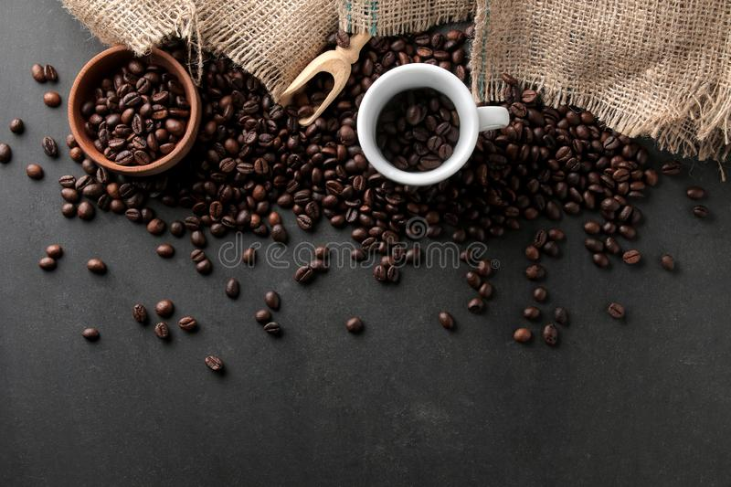 Roasted coffee beans in a cup and wooden spoon on a black background. Robusta, Arabica. top view stock photo