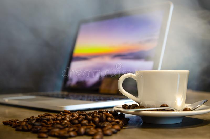 Roasted coffee beans and espresso in a cup of hot coffee with hot steam and smoke, black background,workplace in a cafe shop,a cup stock images