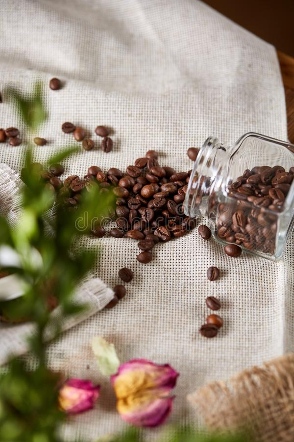 Roasted coffee beans get out of overturned glass jar on wooden background, selective focus, side view royalty free stock photos
