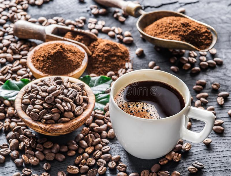 Roasted coffee beans, ground coffee and cup of coffee on wooden royalty free stock photography