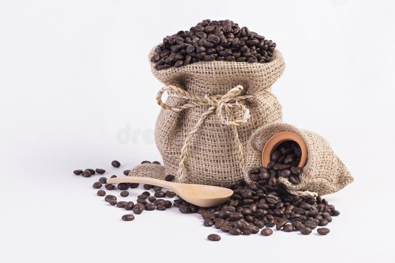 Roasted coffee beans in hemp sacks and wooden spoon on white background. stock photos