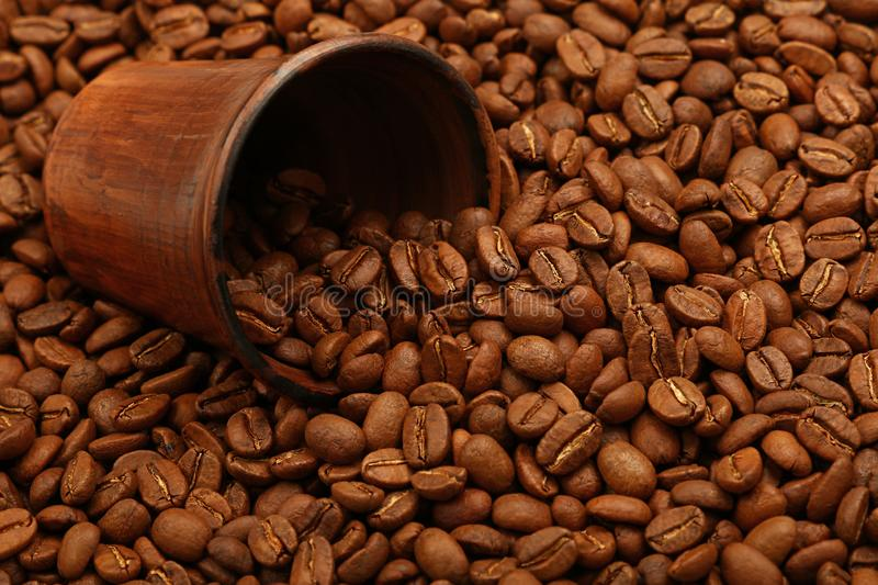 Roasted coffee beans out of brown ceramic cup royalty free stock images