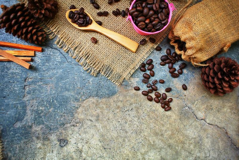 Roasted coffee beans in a pink zinc bucket on a sackcloth background. royalty free stock photography