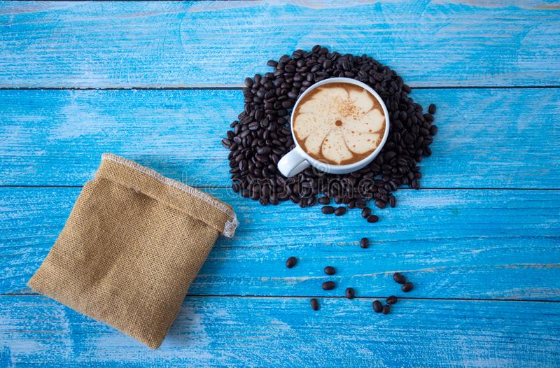 Roasted coffee beans placed on an old blue wooden floor,top view coffee cup for background,Concept:ingredient mocha breakfast royalty free stock images