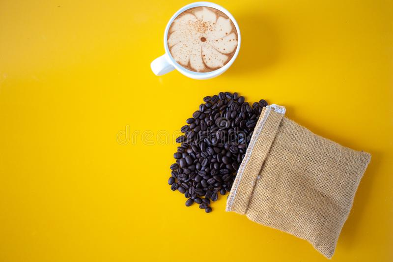 Roasted coffee beans placed on an old Yellow wooden floor,top view coffee cup for background,Concept:ingredient mocha breakfast stock photo