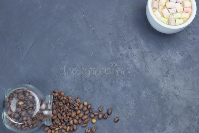 Roasted coffee beans, poured from a glass jar with a white cup of coffee and marshmallow. angular placement of the coffee object. stock images