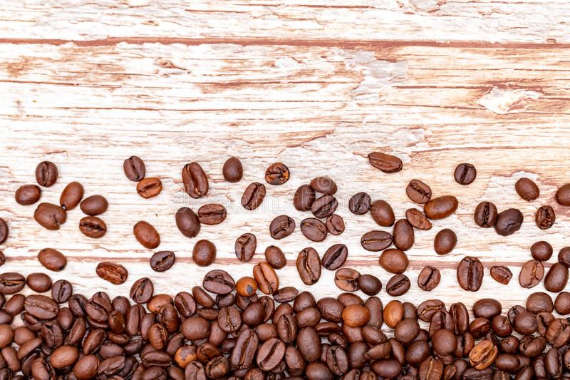 Roasted coffee beans scattered on a background with a wood texture. coffee mania. Close up stock photography