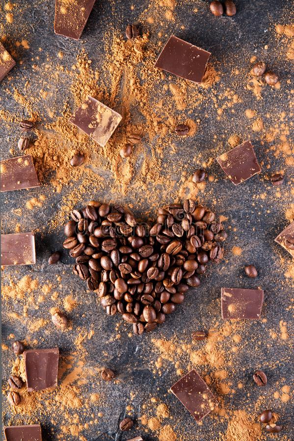 Roasted coffee beans in the shape of a heart on the dark stone background with dissipate cocoa, pieces of chocolate and beans. Sel. Ective focus. Coffee love stock photography