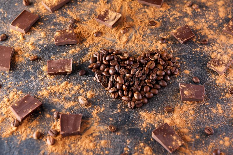 Roasted coffee beans in the shape of a heart on the dark stone background with dissipate cocoa, pieces of chocolate and beans. Sel. Ective focus. Coffee love royalty free stock image
