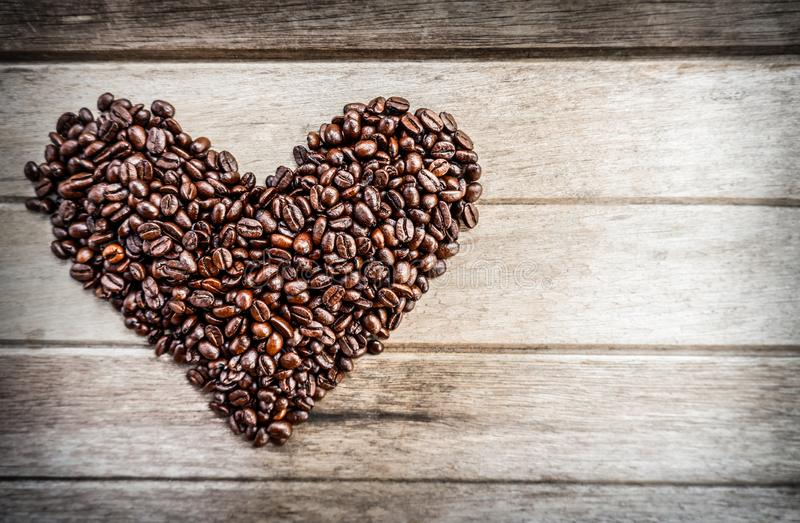 Roasted coffee beans in the shape of heart on a wooden background in the left part of the frame with copy space stock photography